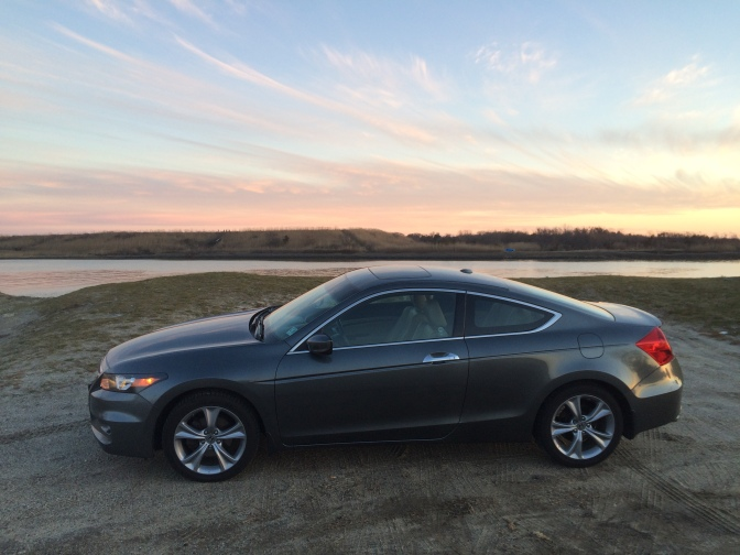 Photo of gray Honda Accord in front of inlet at sunset