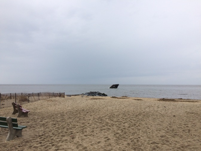 Photograph of beach on cloudy day, wreck of Atlantus is background