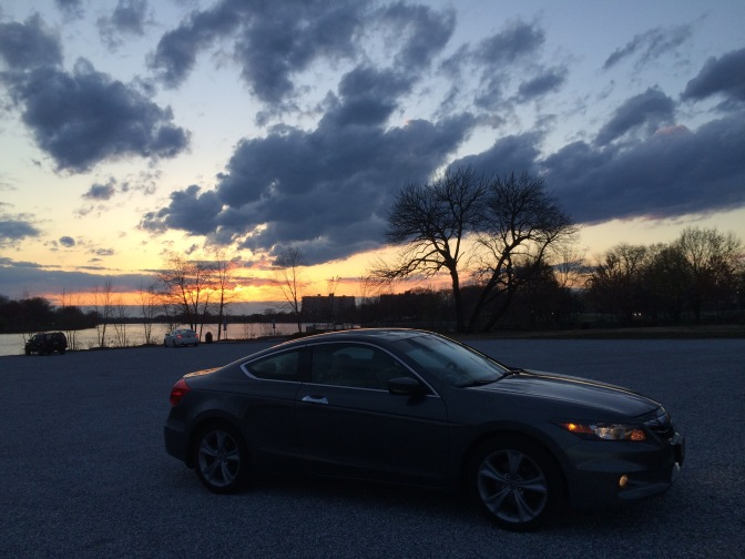 Gray Honda Accord in front of sunset sky.