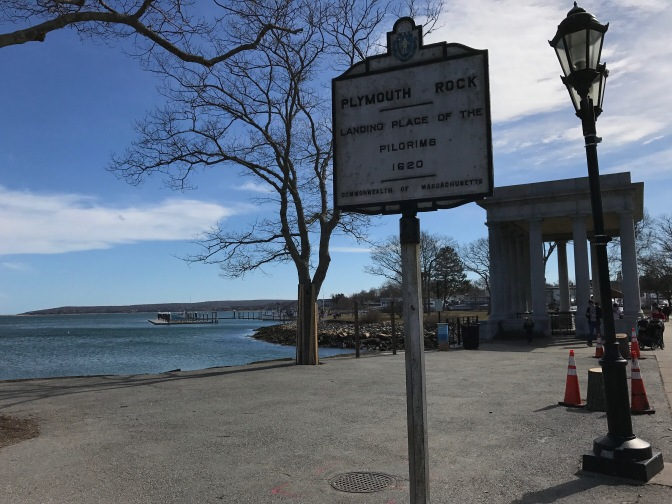 Sign indicating location of Plymouth Rock, with portico in the background.