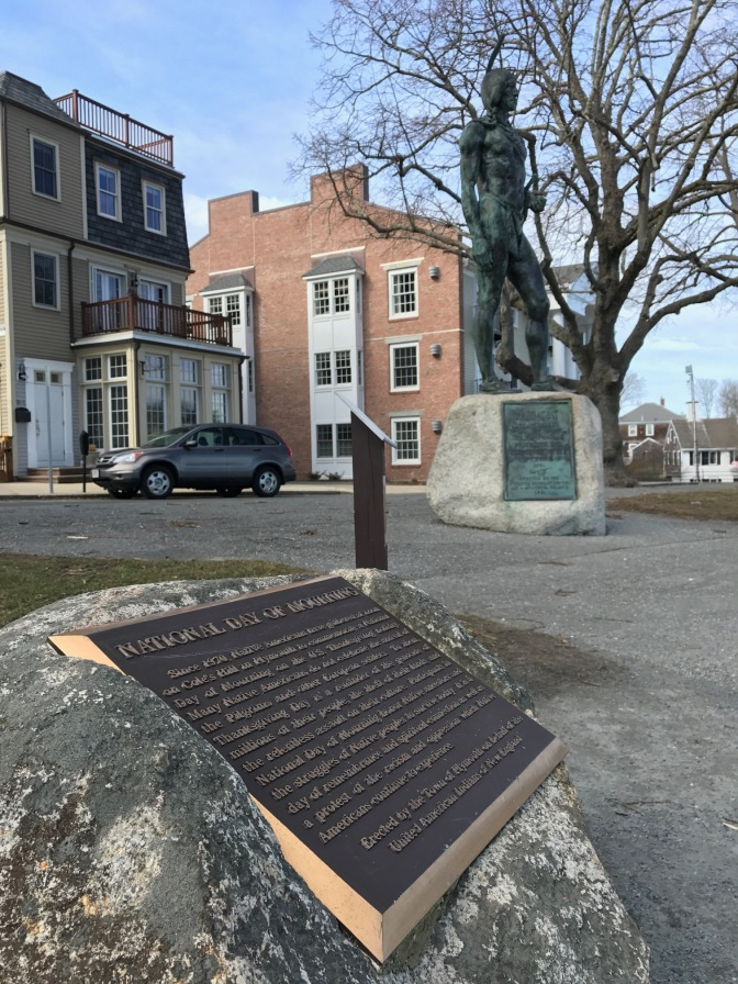 Statue of Massasoit with plaque in the foreground.