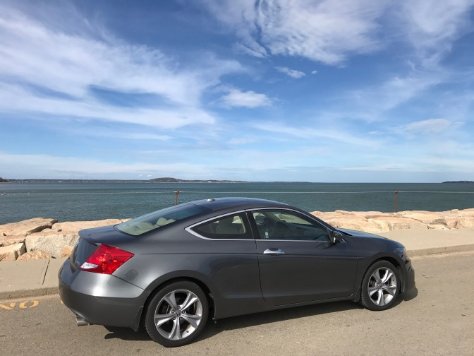 Gray Honda Accord in front of Massachusetts Bay shoreline.