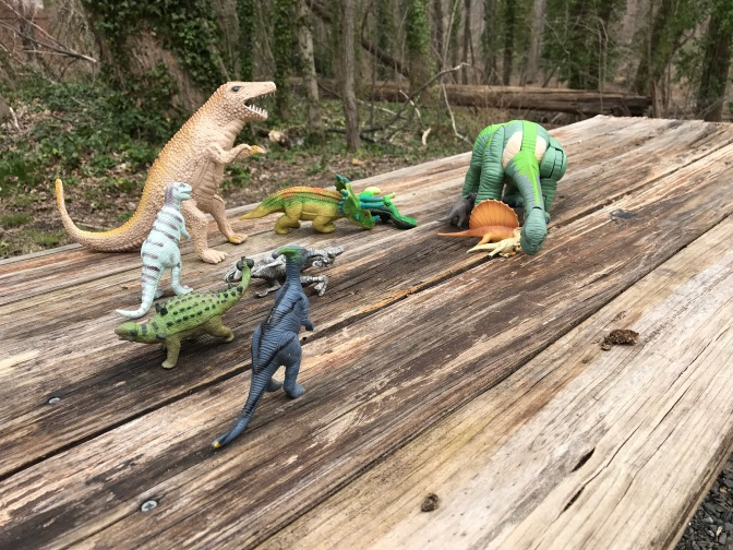 Photo of toy dinosaurs on a wood bench.
