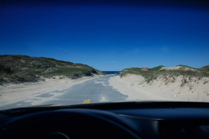 View through car windshield of dunes.