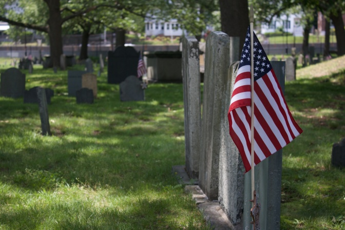 Row of tombstones with American flag in the foreground.