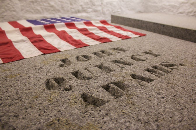 Tomb of John Quincy Adams, with a flag at the head of the tomb.