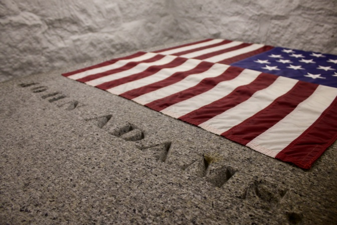Tomb of John Adams with US flag at head of tomb.