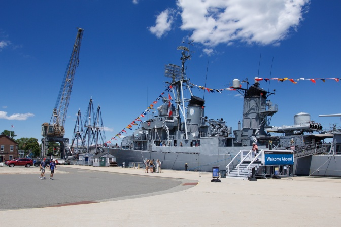 USS Cassin Young at dock. A gantry crane is beside it.