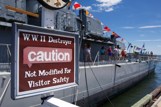 "Sign that says ""WWII Destroyer CAUTION Not Modified for Visitor Safety"" in front of ship."