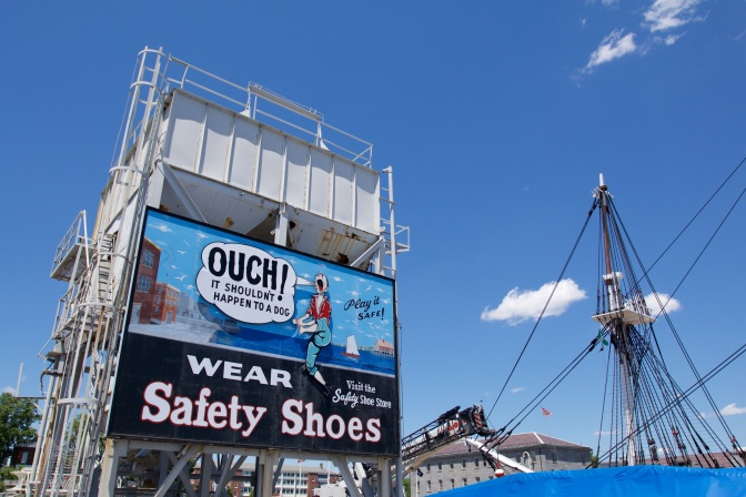 "Billboard on building in shipyard. Text says ""Ouch! It shouldn't happen to a dog: Wear Safety Shoes: Visit the Safety Shoe Store"" and shows a sailor holding his foot, in pain."