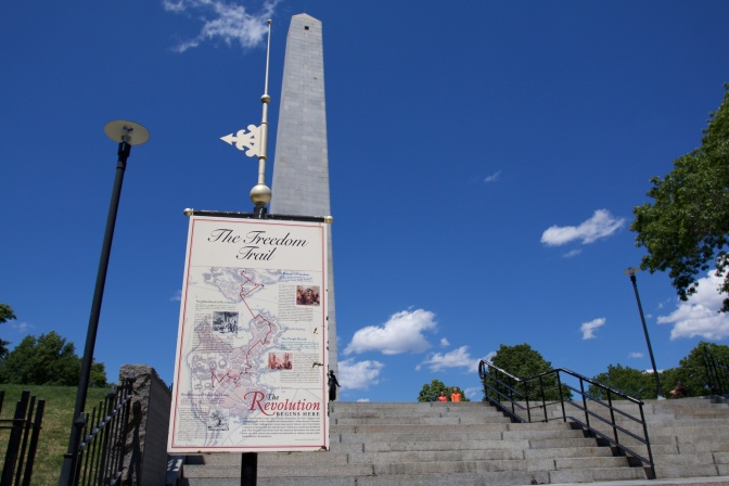 Map of the freedom trail on a post, with the Bunker Hill Monument in the background.