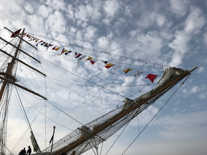 View of the foremast, bowsprit, and flags on the Chilean barquentine Esmeralda.