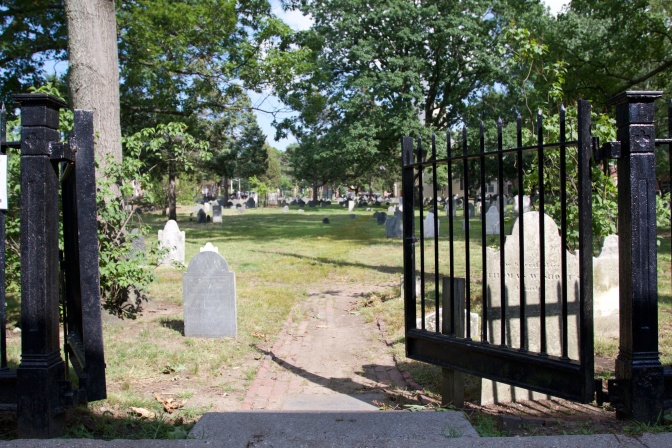 Entrance to Cambridge Burial Grounds. A gate is in the foreground.
