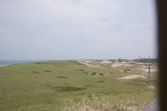 View of the dunes and the sea, through a window.