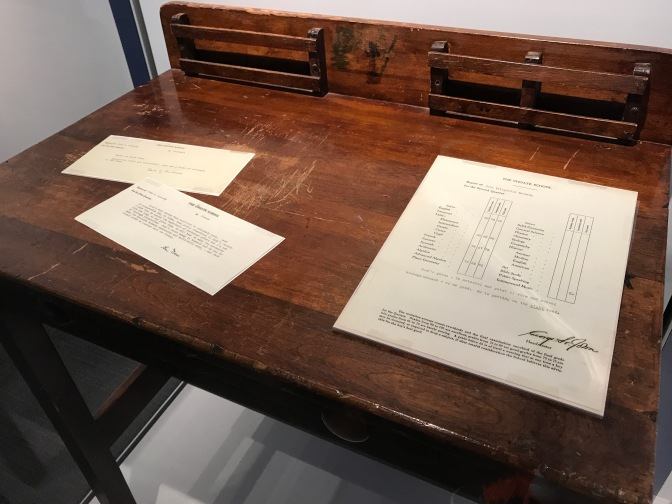 Picture of school desk with John's report card and letters from the headmaster.