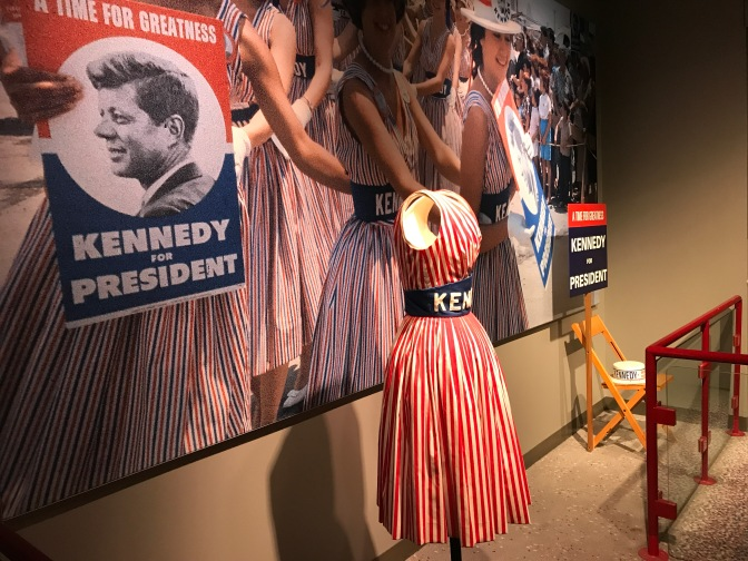 Display with photo of women wearing red and blue dresses with the word KENNEDY on a sash on them. A dress is on display in front of the photo.