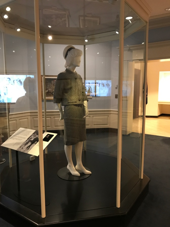 Mannequin of Jackie Kennedy, with a tweed skirt and jacket, on display in a glass case.