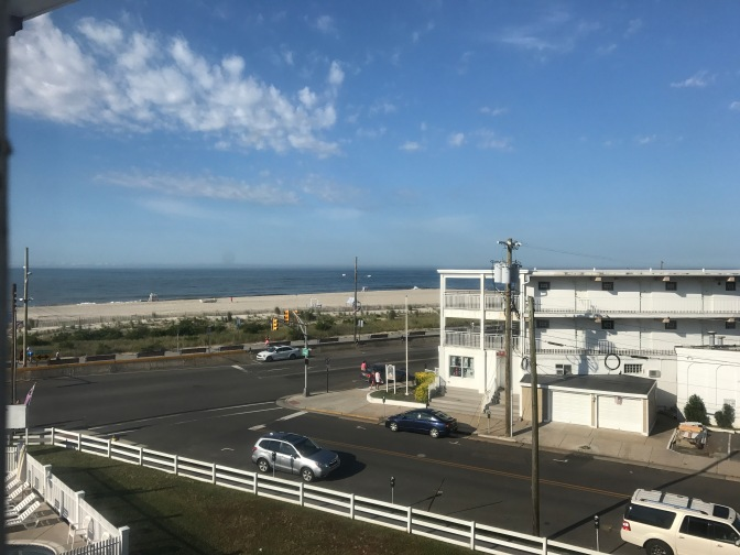 View of the Cape May beach through a hotel window. A street is in the foreground.