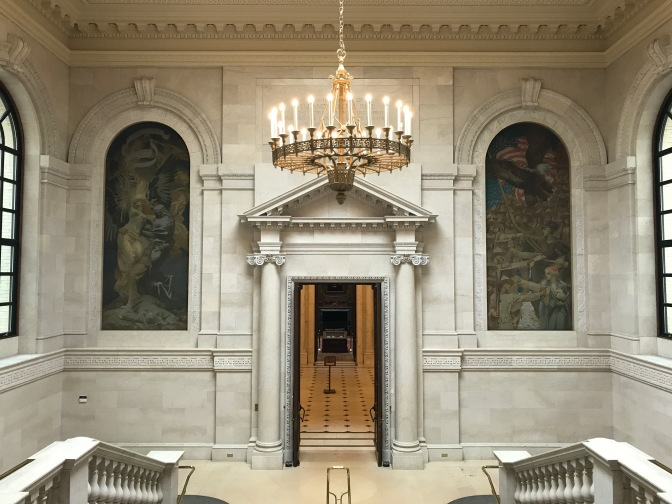 View of hallway in Widener Library. A chandelier hangs from the ceilings a door is in the center of the room, and two tapestries depicting WWI are on either side of the door.