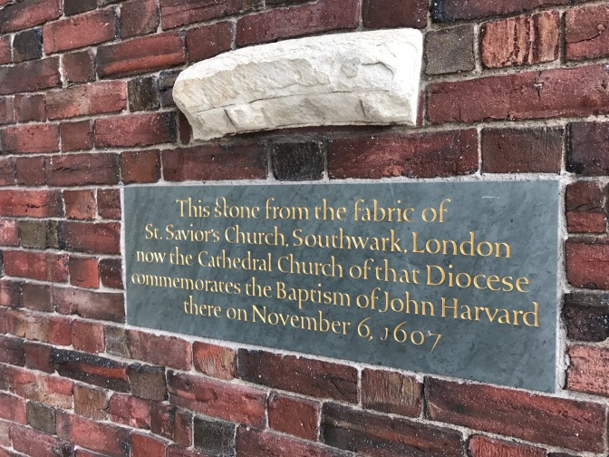 "Wall of Memorial Church at Harvard. A piece of white stone is attached to the brick wall. The inscription below it reads: ""This stone from the fabric of St. Savior's Church, Southwark, London, now the Cathedral Church of that Diocese commemorates the Baptism of John Harvard there on November 6, 1607."