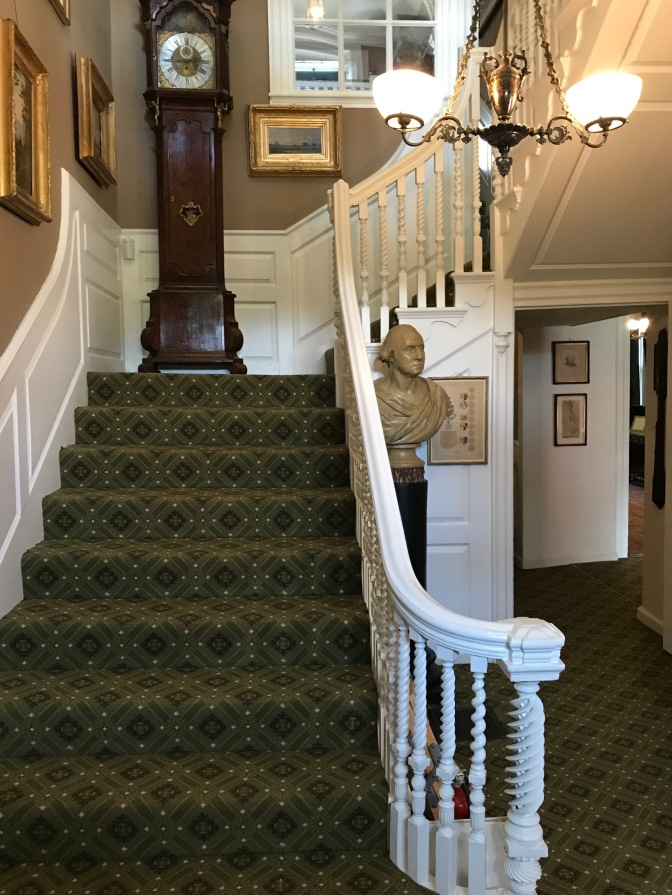 Main staircase. A grandfather clock is on the landing, and several paintings are on the walls.