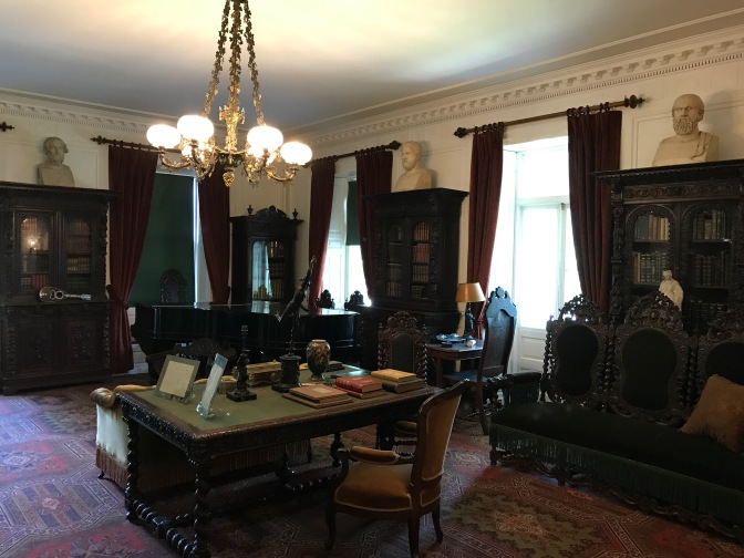Library of the Longfellow House. A desk is in the foreground, a piano is in the background, and numerous bookshelves line the walls.