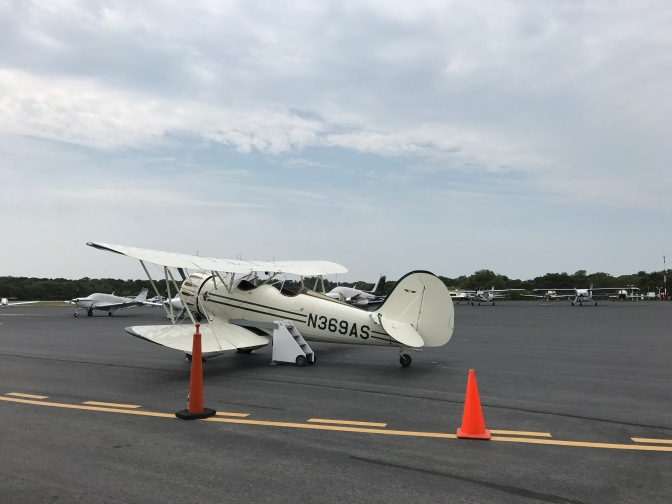 White biplane sitting on tarmac. Several airplanes are parked in the background.