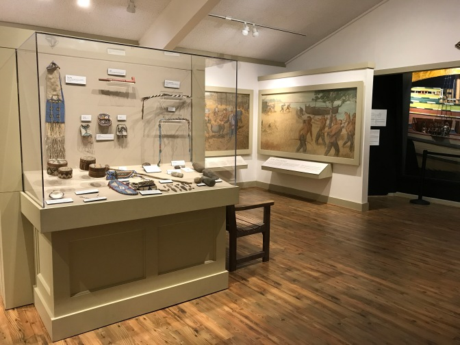 In the foreground, a display of Native American jewelry and other items. In the backgrounds mural depicting the first contact with Native Americans by the Pilgrims.