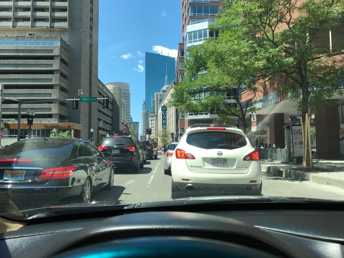 View from behind windshield of traffic in Boston. City buildings are in the background.