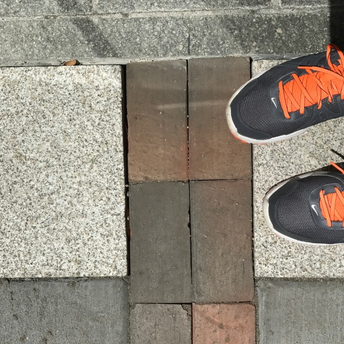 Sneakers next to red brick path of freedom trail.