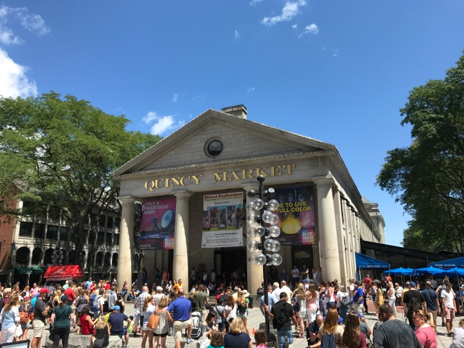 Tourists watching a street performer in front of Quincy Market.