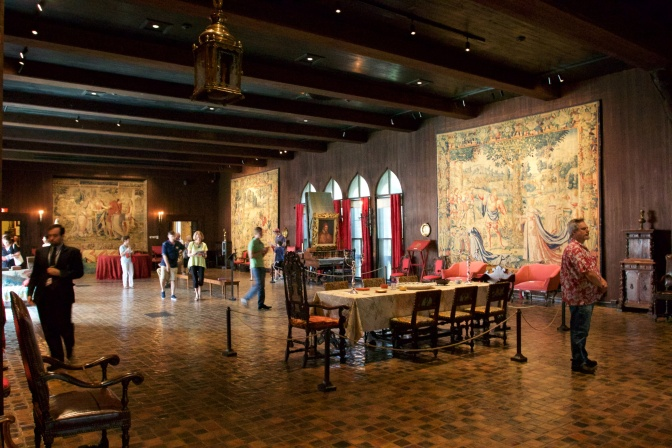 The Tapestry Room. Tapestries hang on the walls, a dinner table with chairs in in the center of the room. People are milling about the room.