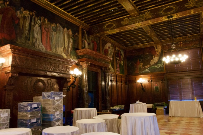 The Abbey Room. Murals are on the walls. Tables with tablecloths are in the foreground.