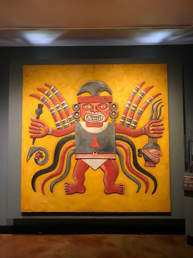 Mural of Decapitator God, from Peru. The deity holds a dagger in his right hand and a decapitated head in his left.
