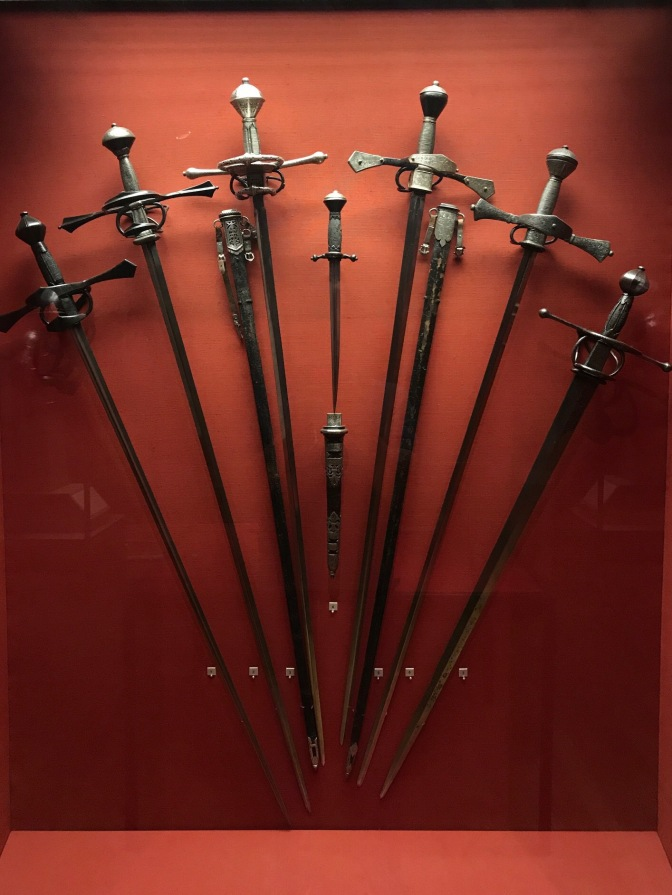Collection of swords hanging on a wall display.