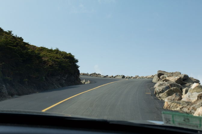 Paved mountain road, with rocks along the edge of the road on the right.