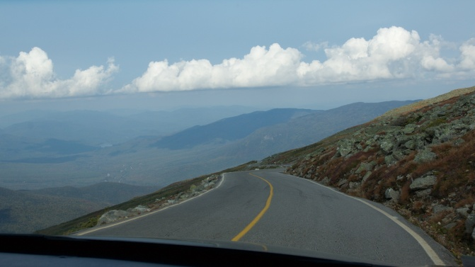 View of the road while descending the mountain by car. Clouds are in the distance.
