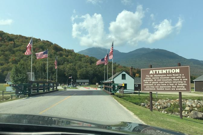 Entrance to Mt. Washington Auto Road. Flags line the roadway, and the mountain peak is in the dance.