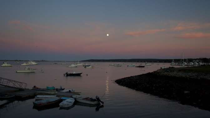 Plymouth Harbor. The moon is in the sky above the harbor.