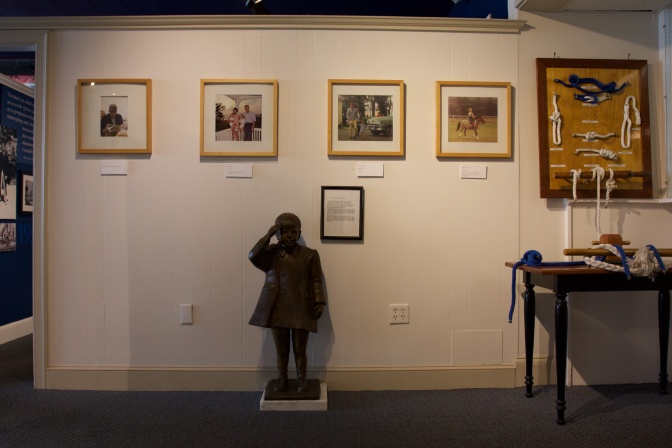 Display of photos of President Kennedy, nautical knots, and a statue of his son standing at attention.