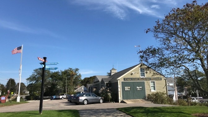Cape Cod Maritime Museum. Cars are parked in the lot in front of the museum, and a flag flies on the left of the image.