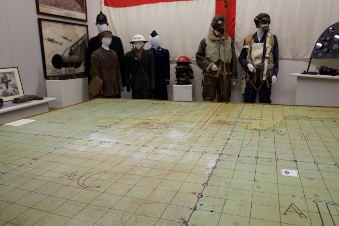 Air map table and mannequins of pilots in uniform.