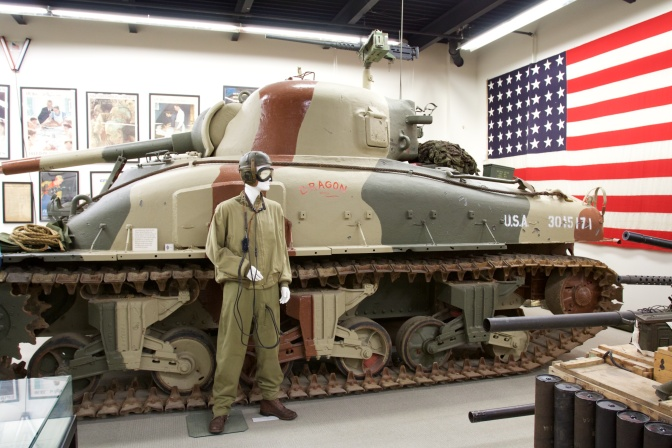 M4 Sherman tank, with mannequin dressed as tank commander in front of it.