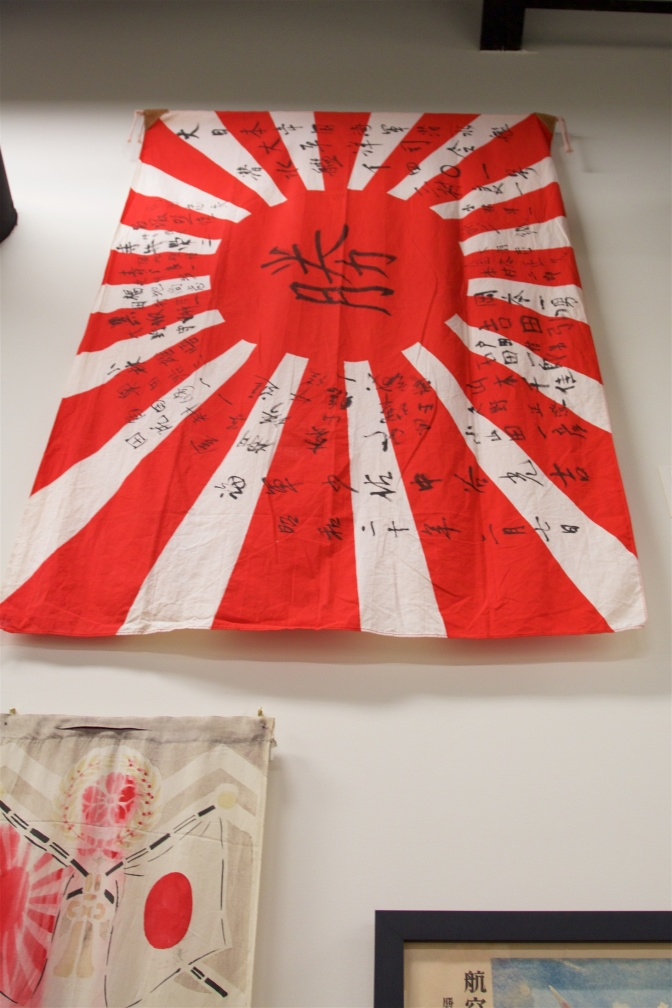"Japanese flag signed by captain and crew of a submarine, with the word ""victory"" in Japanese in the middle."