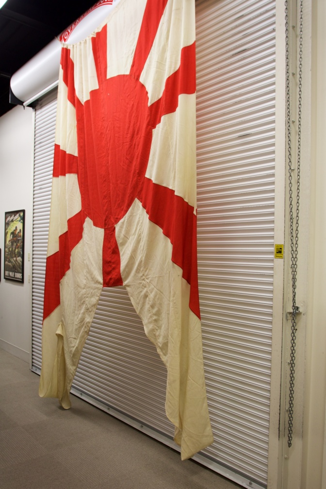 Large Japanese flag hanging on a wall.