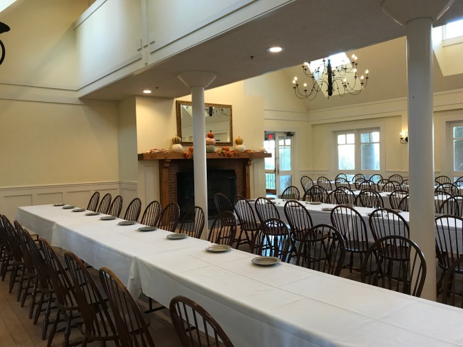 Dining room at the visitor center, with four rows of tables and chairs being set for mealtime.