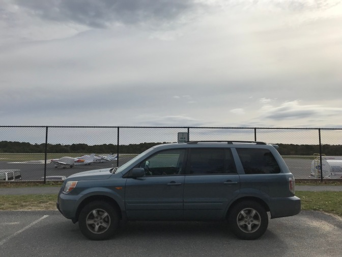 2007 Honda Pilot parked in front of airport fence.