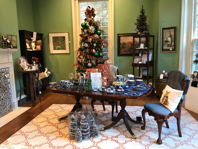 Interior of the gift shop. A table in the foreground has items for sale. A Christmas tree is in the background.