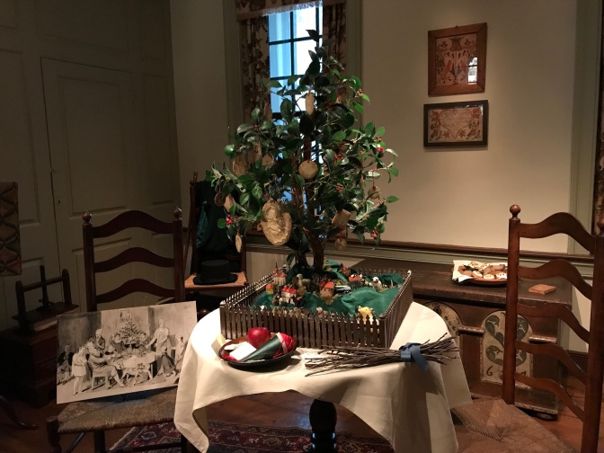 A small Christmas tree on a table is decorated with Christmas cookies.