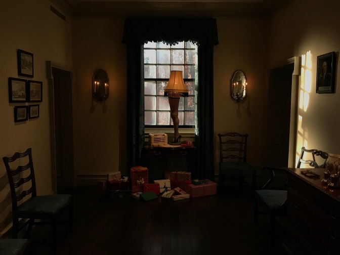 Leg lamp on a table by the window. Presents are on the floor.
